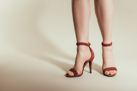 cropped image of woman legs in stylish high heeled sandals on white background