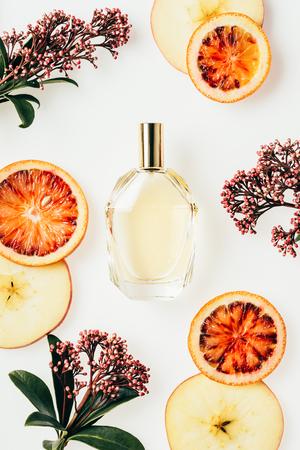 Vista superior del frasco de vidrio de perfume rodeado de frutas y flores en blanco