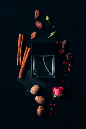 top view of bottle of perfume surrounded with aromatic spices on black