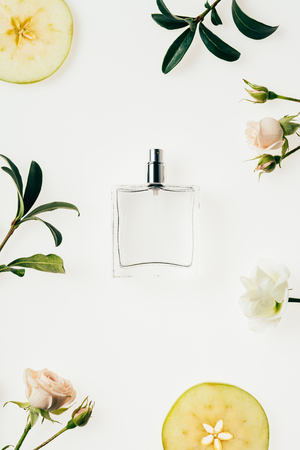 top view of glass bottle of perfume surrounded with flowers and apple slices on white