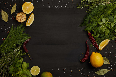 flat lay with citrus fruits, chili peppers, bay leaves, spices, rosemary and parsley on black surface
