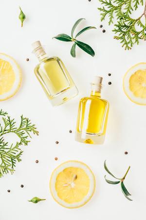 bovenaanzicht van flessen vers parfum met groene takken en schijfjes citroen op wit Stockfoto