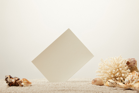 close up view of coral, seashells and blank card on sand on grey background Banco de Imagens
