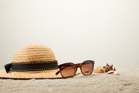 close up view of straw hat, sunglasses and seashells on sand on grey backdrop Фото со стока