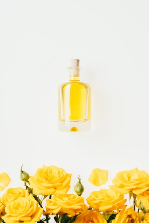 top view of bottle of perfume and yellow roses on white