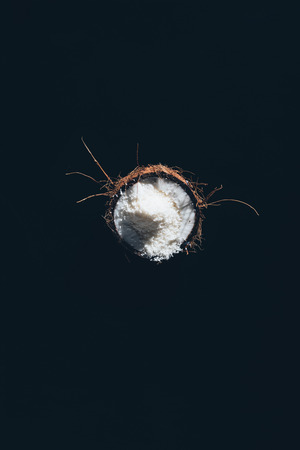 top view of half of coconut with tasty healthy shavings isolated on black