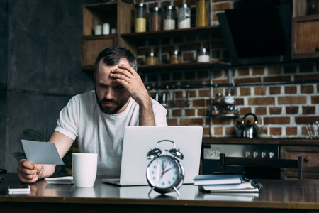 depressed young man looking at photo card in hand while sitting at kitchen with laptop and alarm clock