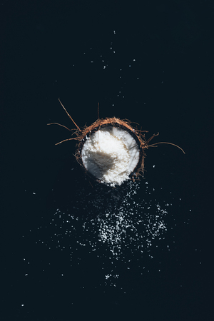 top view of fresh healthy coconut with shavings on black Фото со стока