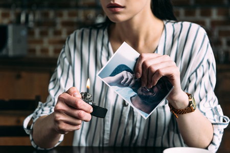 cropped shot of young woman burning photo card of ex-boyfriend