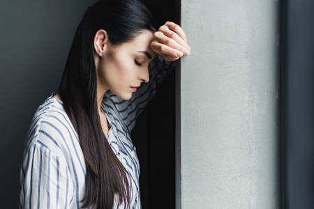 side view of depressed young woman leaning on wall with closed eyes