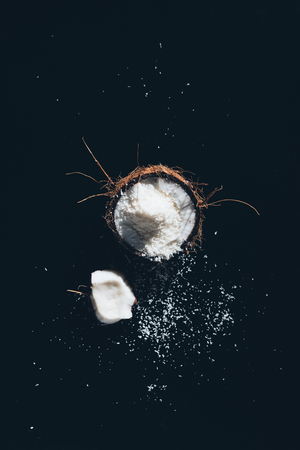 top view of fresh organic coconut with shavings on black