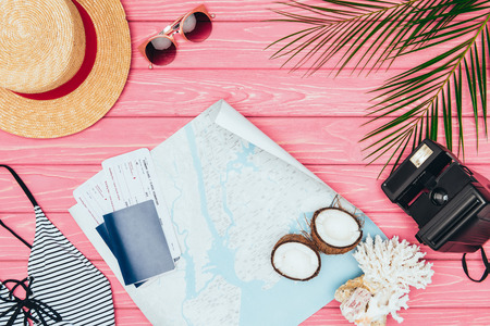 top view of map and flight tickets surrounded with travel attributes on pink wooden surface Stock Photo - 106593868