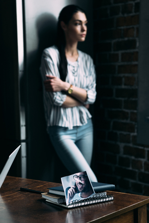 depressed young woman standing alone and looking away with photo of ex-boyfriend on foreground Stock Photo