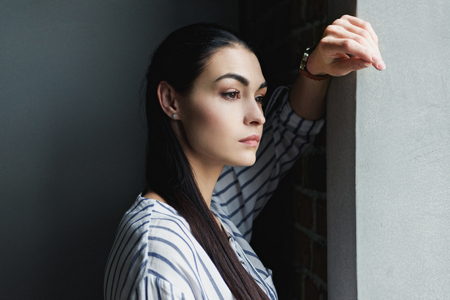 side view of depressed young woman leaning on wall and looking away