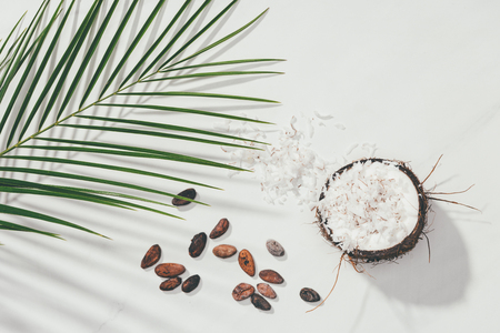 top view of half of coconut with shavings and cocoa beans with green palm leaves on white Stock fotó