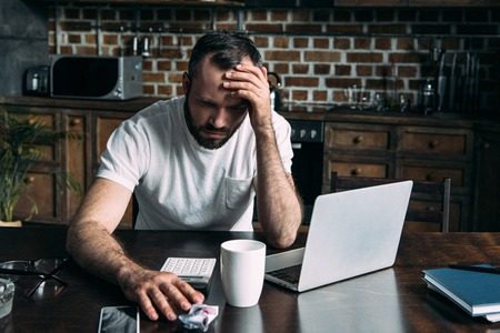 depressed young man sitting on kitchen with laptop and crumpled photo of ex-girlfriend Stock Photo