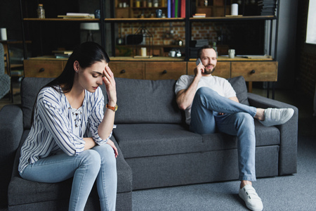 sad woman sitting on couch while her husband talking by phone blurred on background