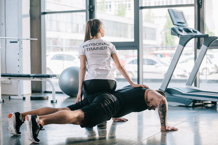 sportsman doing push ups with female personal trainer sitting on his back at gym