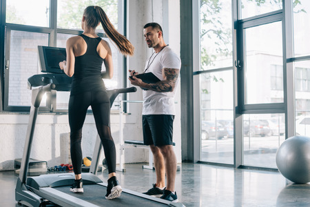 male personal trainer using timer while sportswoman running on treadmill at gym Zdjęcie Seryjne