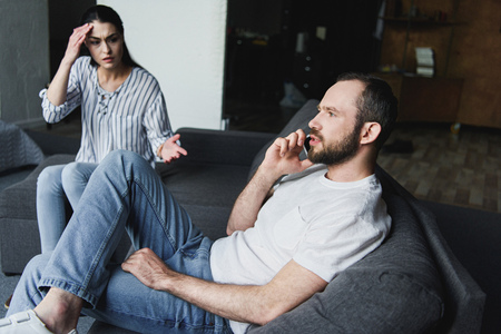 mad woman talking to her husband while he talking by phone on couch