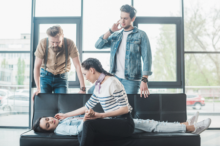 Business colleagues helping young fainted woman lying on sofa in office