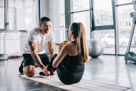 male personal trainer helping sportswoman to do abs with ball at gym Stockfoto