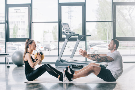 male personal trainer and sportswoman doing exercises with ball at gym Stockfoto