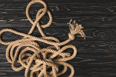 top view of brown nautical rope on dark wooden surface Фото со стока