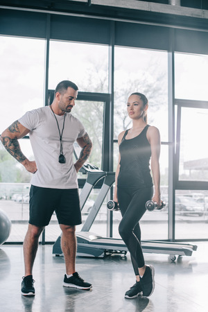male personal trainer looking at sportswoman exercising with dumbbells at gym