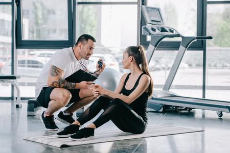 männlicher persönlicher Trainer, der Zeitgeber zu junger athletischer Frau auf Fitnessmatte im Fitnessstudio zeigt