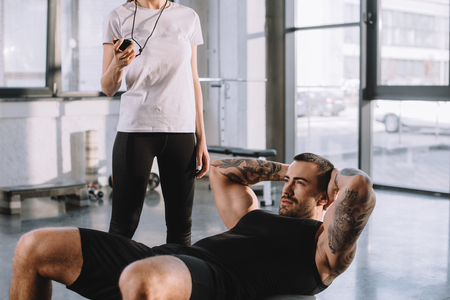 female personal trainer using timer while sportsman doing abs at gym Stockfoto