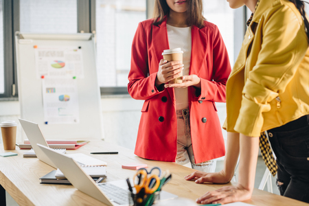 Businesswoman holding coffee cup and listening to her colleague in workspace