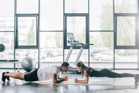 male personal trainer and sportswoman doing plank at gym