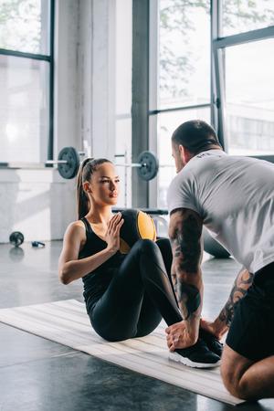 mannelijke persoonlijke trainer die Sportvrouw helpt om abs met bal te doen op sportschool Stockfoto