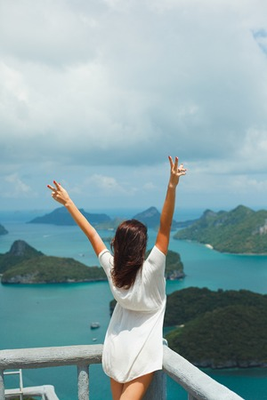 back view of woman standing with hands up at Ang Thong National Park, Ko Samui, Thailand