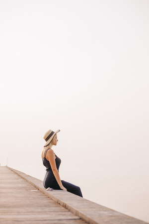 side view of beautiful woman in hat and dress sitting on pier near ocean