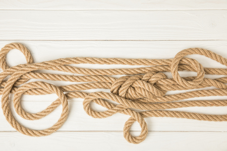 top view of brown nautical knotted ropes on white wooden surface