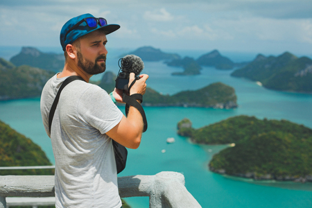 tourist shooting video with camera of islands in ocean at Ang Thong National Park, Ko Samui, Thailand