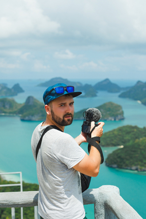 handsome man shooting video with camera of islands in ocean at Ang Thong National Park, Ko Samui, Thailand