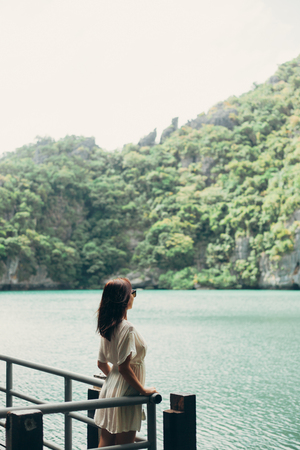 side view of traveler standing on pier near bay at Ang Thong National Park, Ko Samui, Thailand