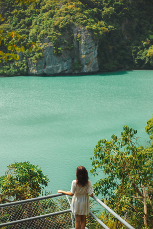 back view of woman looking at rocky island at Ang Thong National Park, Ko Samui, Thailand Stock Photo