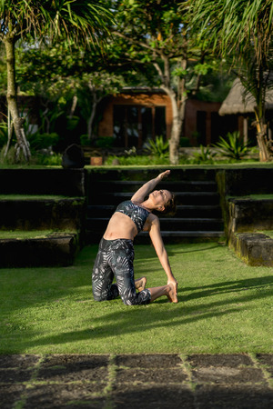 woman practicing yoga in Camel Pose with beautiful green plants on background, Bali, Indonesia