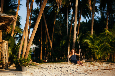 attractive woman on swing between palm trees at beach