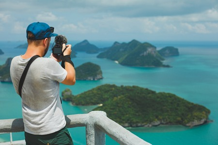 back view of tourist shooting video with camera of islands in ocean at Ang Thong National Park, Ko Samui, Thailand Stock Photo
