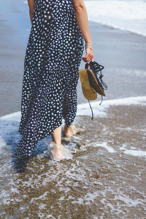 cropped view of barefoot girl in long dress holding shoes and walking in water in sea
