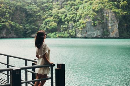 side view of woman standing on pier near bay at Ang Thong National Park, Ko Samui, Thailand Banco de Imagens