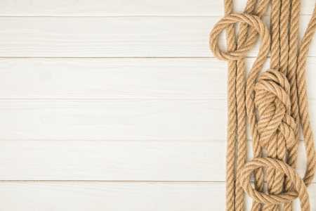 top view of brown nautical knotted ropes on white wooden background Stock Photo