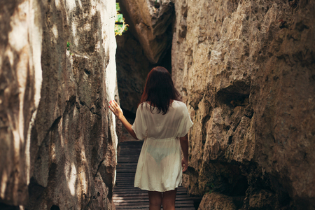 rear view of woman walking between cliffs at Ang Thong National Park, Ko Samui, Thailand Stock Photo