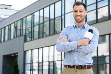 cheerful male journalist posing with microphone outside Stock Photo