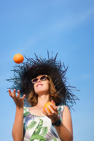 bottom view of beautiful young woman in hat juggling with oranges against blue sky